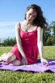 Lady with female magazine sitting on grass — Stock Photo