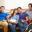 Group Of Friends Sitting On Sofa Watching TV Together — Stock Photo #59344383