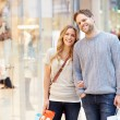 Portrait Of Couple Carrying Bags In Shopping Mall — Stock Photo #59344909