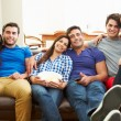 Group Of Friends Sitting On Sofa Watching TV Together — Stock Photo #59344913