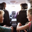 Children In Back Seat Of Car On Journey With Parents — Stock Photo #59344979