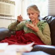 Senior Woman With Poor Diet Keeping Warm Under Blanket — Stock Photo #59345925