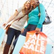 Two Female Friends With Bags In Shopping Mall — Stock Photo #59346131