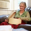 Senior Woman Keeping Warm Under Blanket With Memory Box — Stock Photo #59346489
