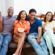 Group Of Friends Sitting On Sofa Watching TV Together — Stock Photo #59347119