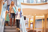 Mother And Children On Escalator In Shopping Mall — Stock Photo