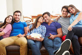 Group Of Friends Sitting On Sofa Watching TV Together — Stock Photo