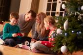 Family Unwrapping Gifts By Christmas Tree — Stock Photo