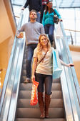 Female Shopper On Escalator In Shopping Mall — Stock Photo