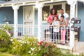 Portrait Of Family Standing On Porch Of Suburban Home — Stock Photo