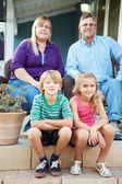 Portrait Of Family Sitting Outside House — Stock Photo