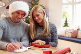 Couple Wrapping Christmas Gifts At Home — Stock Photo