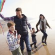 Family Running with Flying Kite — Stock Photo #59877537
