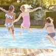 Girls Jumping Into Swimming Pool — Stock Photo #59877685