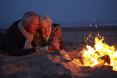 Senior Couple Sitting By Fire — Foto de Stock