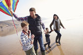 Family Running with Flying Kite — Foto Stock