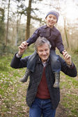 Grandfather Carrying Grandson On Shoulders — Stockfoto