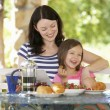 Mother and daughter eating breakfast — Stock Photo #61028215