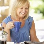 Senior woman eating breakfast — Stock Photo #61028403