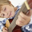 Boy playing acoustic guitar — Stock Photo #61029891