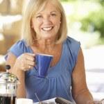 Senior woman eating breakfast — Stock Photo #61029917