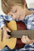 Boy playing acoustic guitar — Stock Photo