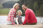 Family sitting on a jetty — Stock Photo