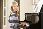 Girl playing grand piano — Stock Photo