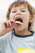 Boy eating crisps — Stock Photo