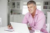 Mid age man working on laptop — Stock Photo