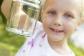 Girl with cricket in a jar — Stock Photo