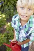 Boy watering garden — Stock Photo