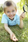Young boy with  magnifying glass — Stock Photo