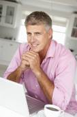 Mid age man working on laptop — Stock Photo