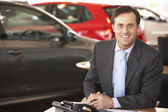 Man in car showroom — Stock Photo