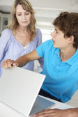 Mother supervising son using laptop — Stock Photo