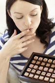 Woman eating chocolates — Stock Photo