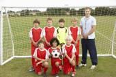 Junior football team and coach portrait — Stock Photo