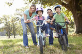 Parents with children on bikes — Stock Photo