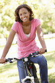 Woman cycling in park — Stock Photo
