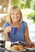 Senior woman eating breakfast — Stock Photo