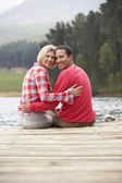 Romantic couple on a jetty — Stock Photo