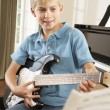 Boy playing electric guitar at home — Stock Photo #61031123
