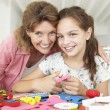 Girl doing handicrafts with grandmother — Stock Photo #61032395
