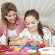 Girl doing handicrafts with grandmother — Stock Photo #61032777