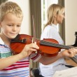 Young boy playing violin accompanied by teacher — Stock Photo #61032837