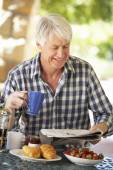 Middle aged man eating breakfast — Stock Photo