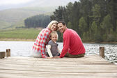 Family sitting on a jetty — Stock fotografie