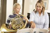 Girl playing French horn in music lesson — Stock Photo