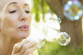 Senior woman blowing bubbles — Stock Photo